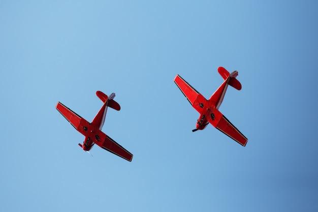 Twee rode vliegtuigen in de blauwe hemel