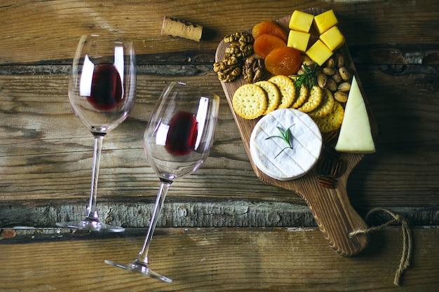 Twee rode wijnglas en kaasschotel bovenaanzicht