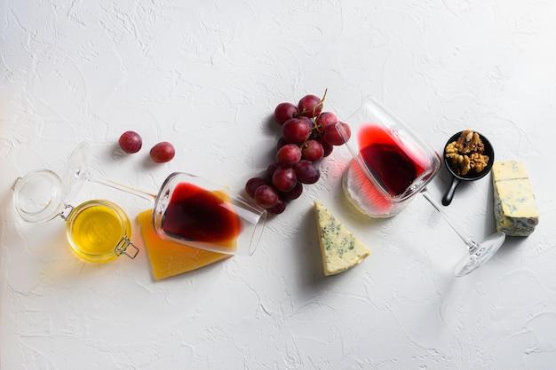 Twee rode wijnglas met diverse kazen