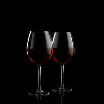 Twee rode wijnglazen in het donker