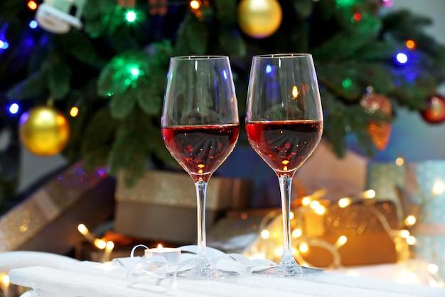 Twee rode wijnglazen tegen kerstboomachtergrond, kerstsfeer,