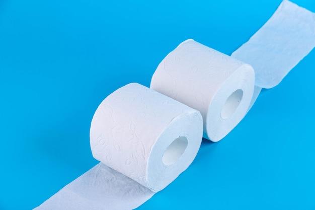 Twee rollen van wit zacht toiletpapier op blauwe achtergrond