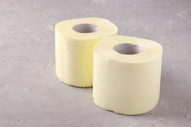 Twee rollen zacht toiletpapier op grijs oppervlak, hoge onverwachte vraag, tekort, covid-19 pandemie