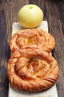 Twee ronde broodjes met jam en appel op houten tafel