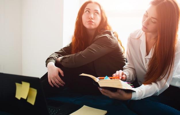 Twee roodharige studenten studeren thuis of in een studentenflat. ze zijn voorbereid op examens. een jonge vrouw verveelt zich en de tweede studente richt zich op studeren.