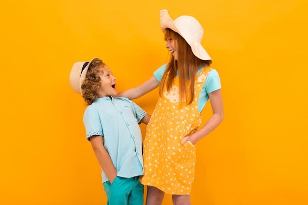 Twee roodharige vrienden in zomerhoeden kijken elkaar op een geel aan