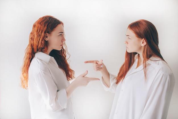 Twee roodharige zussen staan geïsoleerd op een witte achtergrond in ruime oversized shirts. twee jonge meisjes beschuldigen elkaar van hun daden.