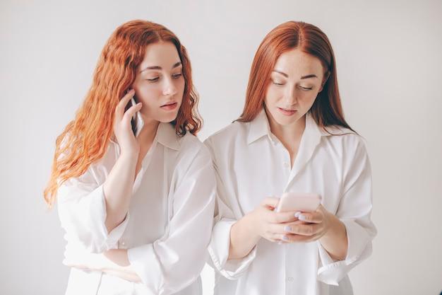 Twee roodharige zussen staan geïsoleerd op een witte achtergrond in ruime oversized shirts. twee jonge vrouwen zijn verslaafd aan sociale netwerken en brengen al hun tijd door op een smartphone