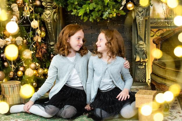 Twee roodharige zusters dichtbij de nieuwjaarsboom.