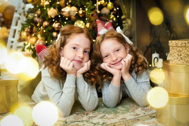 Twee roodharige zusters in de buurt van de kerstboom van het nieuwe jaar