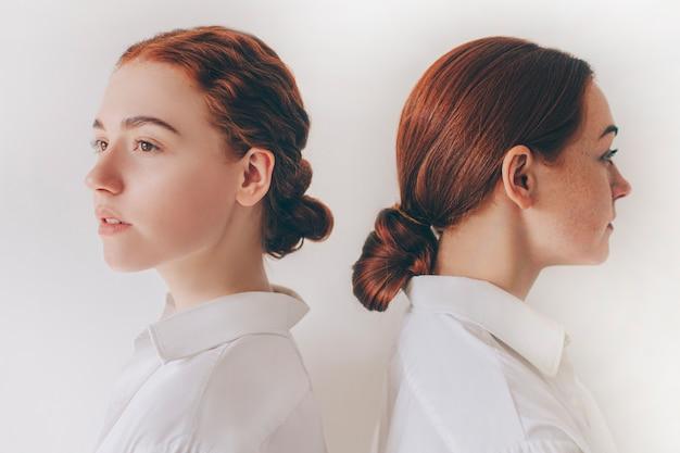 Twee roodharige zusters staan geïsoleerd op een witte achtergrond in overhemden. vrouwen staan met de rug naar elkaar toe. haar is in een bundel gedraaid. ze hebben steil haar en krullende krullen.