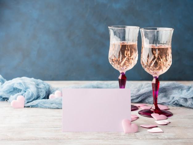 Twee roze champagneglazen met lege document kaart