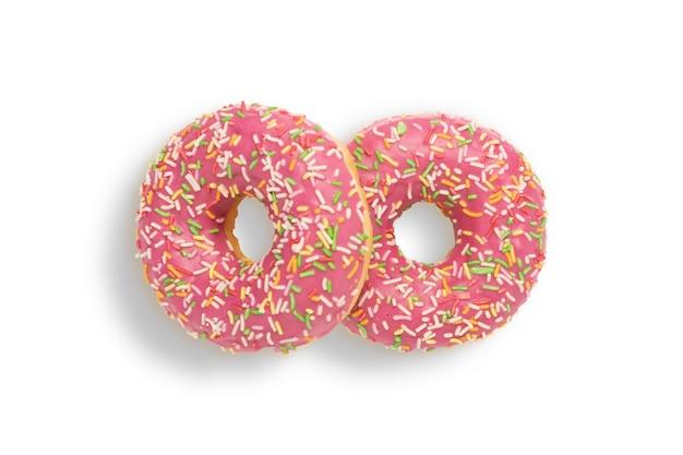 Twee roze donuts met hagelslag op een wit