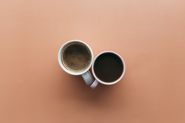 Twee roze en blauwe koffiekopjes op beige achtergrond. hoge kwaliteit foto