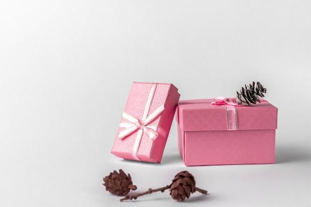 Twee roze geschenkdozen met lint, boog en kegels geïsoleerd op een witte of lichtgrijze achtergrond, natuurlijke schaduw, zijaanzicht. kerst cadeau concept
