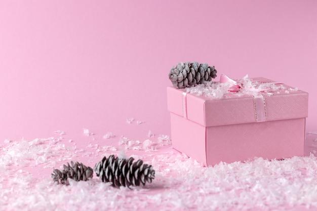 Twee roze geschenkdozen met lint, boog en kegels geïsoleerd op een witte