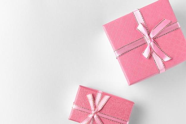 Twee roze geschenkdozen met lint en boog geïsoleerd op een witte of lichtgrijze achtergrond, natuurlijke schaduw, bovenaanzicht