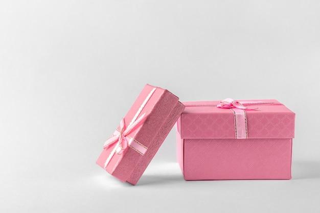 Twee roze geschenkdozen met lint en boog geïsoleerd op een witte of lichtgrijze achtergrond, natuurlijke schaduw, zijaanzicht