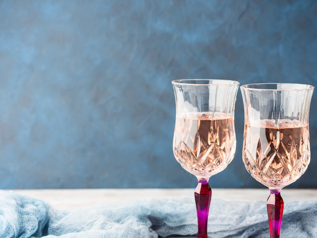 Twee roze gesteelde glazen met champagne