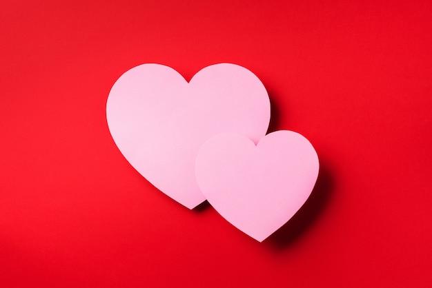 Twee roze harten gesneden uit papier op rode achtergrond met kopie ruimte.