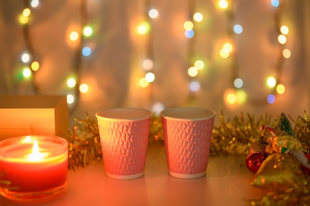Twee roze kopjes op een kerstachtergrond met brandende kaarsen en een gloeiende slinger in warme kleuren. ondiepe scherptediepte.