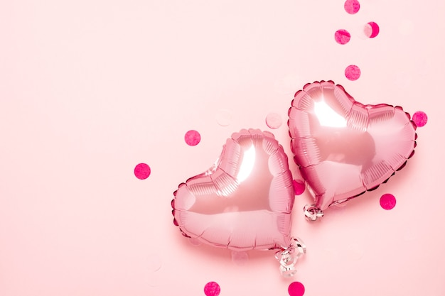 Twee roze luchtballonnen in de vorm van een hart op een roze achtergrond. valentijnsdag, bruiloft decoratie. folie ballen. plat lag, bovenaanzicht