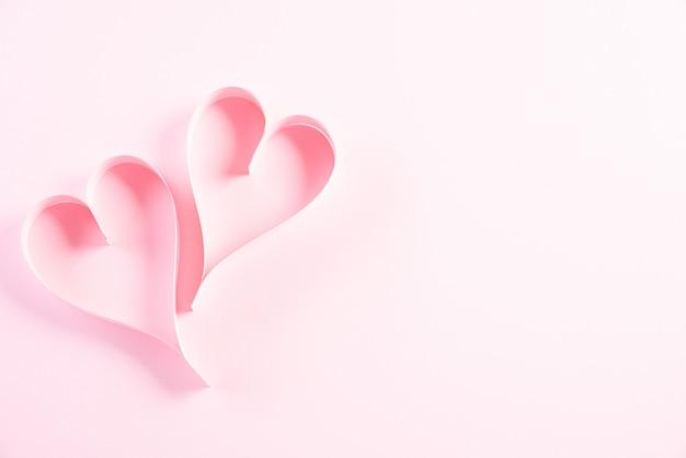 Twee roze papieren harten op papier