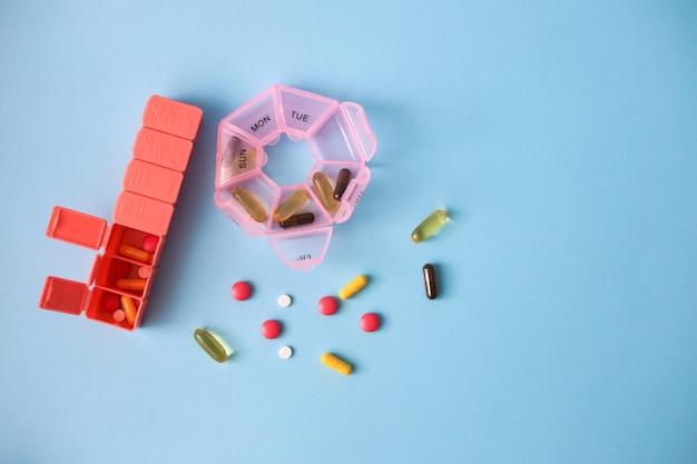 Twee roze pillendoosjes met pillen en capsules