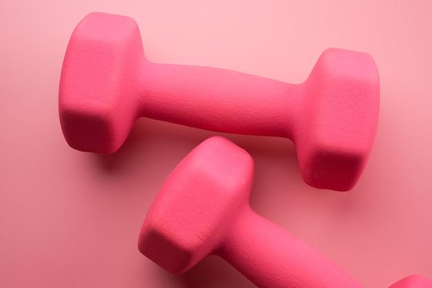 Twee roze vrouwelijke halters geïsoleerd op roze achtergrond close-up met kopie ruimte. fitnessconcept, gewichtsverlies en sportactiviteit, bovenaanzicht, plat leggen