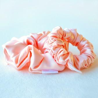 Twee roze zijde scrunchy geïsoleerd op een witte achtergrond kleurrijke elastische haarband vierkante afbeelding