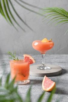 Twee rozemarijn grapefruit frisdrank op grijs.