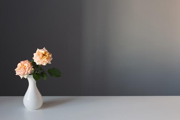Twee rozen in witte vaas op grijze achtergrond