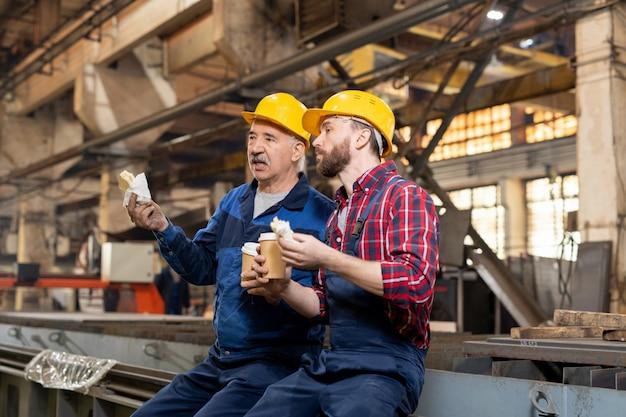 Twee rustgevende technici met drankjes en snacks zitten in de werkplaats en bespreken nieuwe apparatuur tijdens de lunchpauze