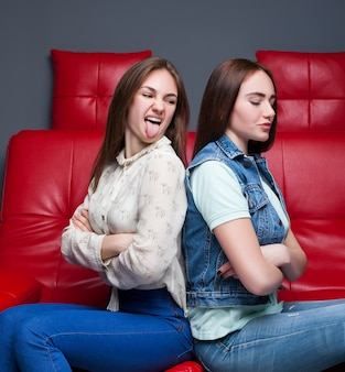 Twee ruziënde meisjes zitten op een rode leren bank. einde van vrouwelijke vriendschap. vrouwen maken ruzie