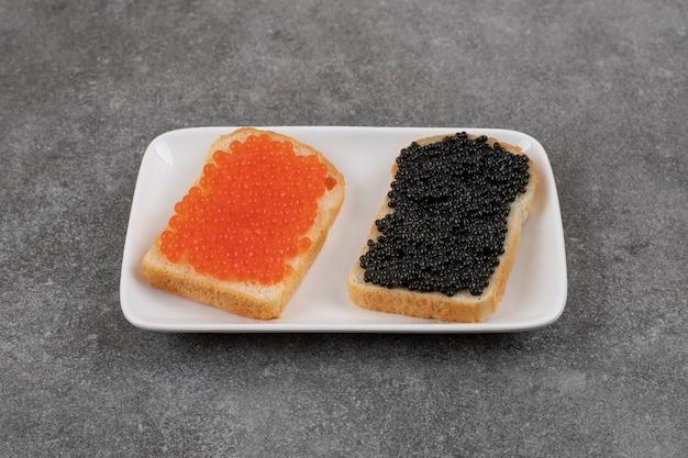 Twee sandwich met rode en zwarte kaviaar op wit zwart.