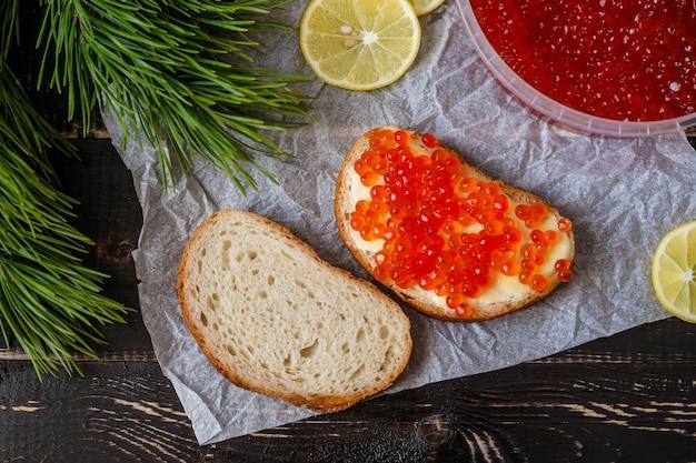 Twee sandwiches met rode kaviaar en citroenen op een zwarte houten achtergrond