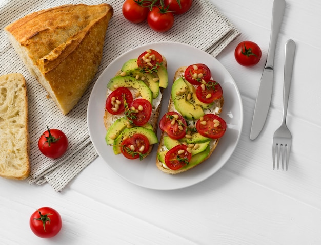 Twee sandwiches of tapas bereid met verschillende groenten, zoals avocado, tomaat en verse tijm sprankelend met pijnboompitten.