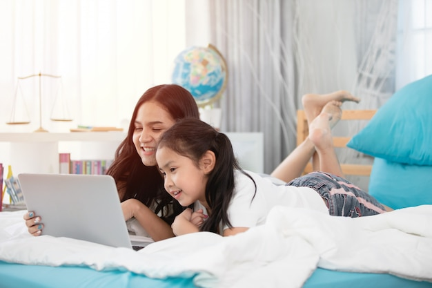 Twee schattige aziatische kindmeisjes die tablet en laptop op bed met behulp van.