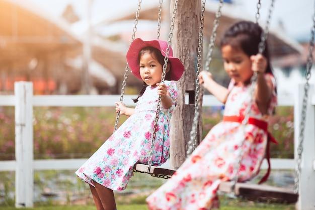 Twee schattige aziatische klein kind meisje spelen schommels samen in de tuin met plezier
