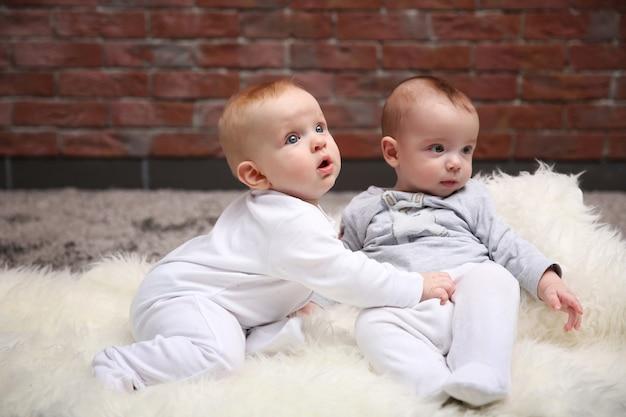 Twee schattige babes spelen in de kamer tegen de achtergrond van een bakstenen muur