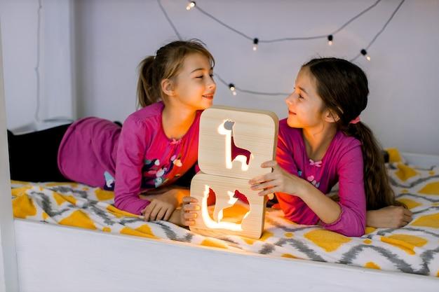 Twee schattige blanke kinderen, mooie kleine meisjeszusjes, gekleed in roze shirts, liggend op een helder kinderstapelbed en spelen met stijlvolle houten nachtlampjes met uitgesneden afbeeldingen.