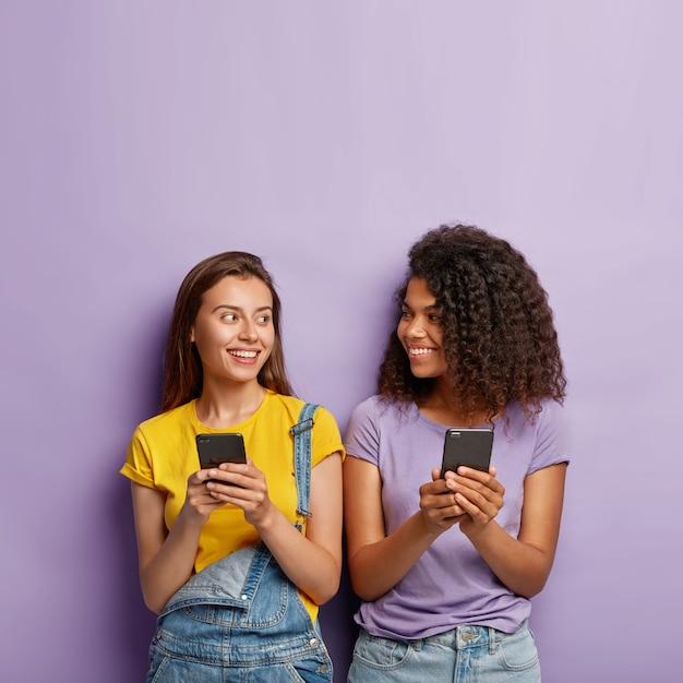 Twee schattige duizendjarige meisjes gebruiken mobiele telefoons