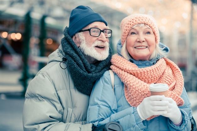 Twee schattige gepensioneerden in warme winterkleren die op straat staan met kopjes koffie en vrolijk glimlachen terwijl ze wegkijken