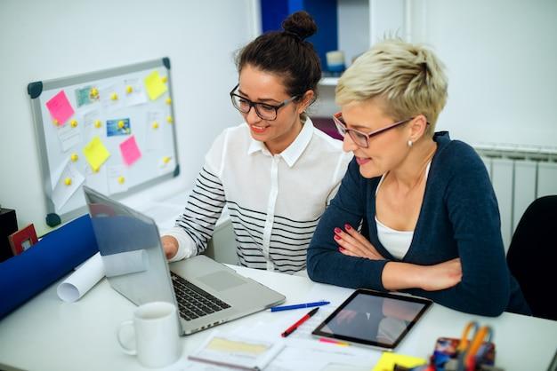 Twee schattige glimlachende vrouwencollega die op laptop en tablet samenwerken terwijl zij op kantoor zitten.