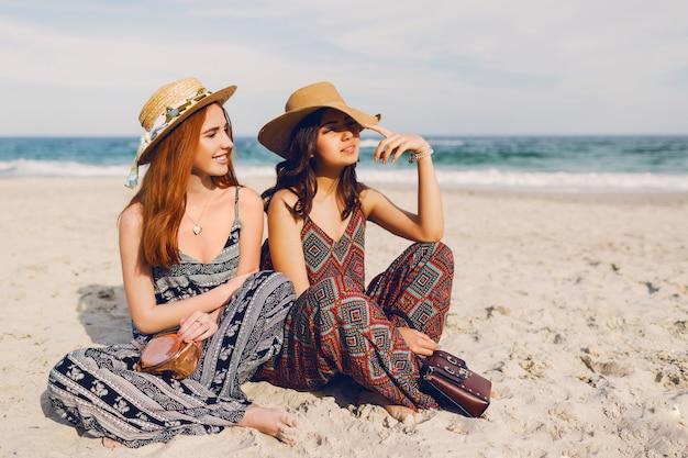 Twee schattige jonge vrouwen die op het strand zitten