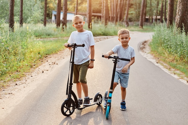 Twee schattige jongens die casual t-shirts en korte broeken dragen, strijden in het rijden op scooters, buiten in het park, zomer, gelukkige broers die samen tijd doorbrengen.