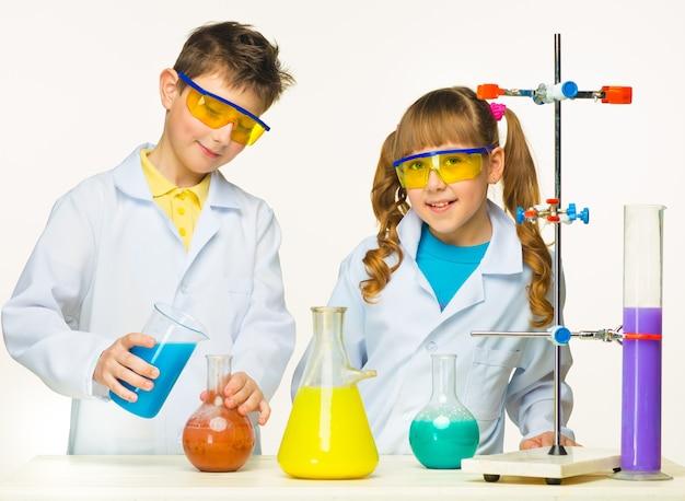Twee schattige kinderen bij scheikundeles die experimenten maken op witte achtergrond