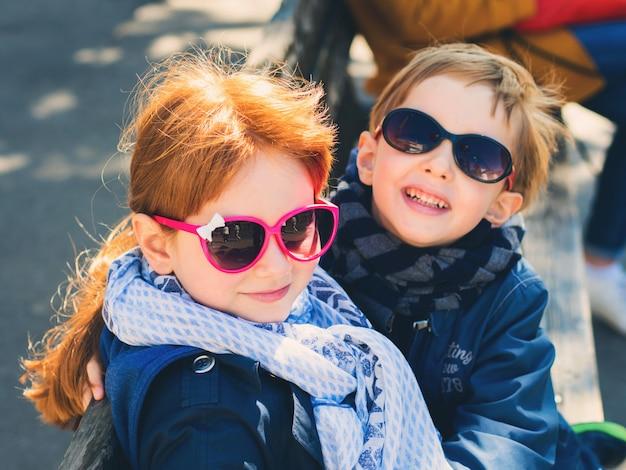 Twee schattige kinderen, broers en zussen knuffelen buitenshuis