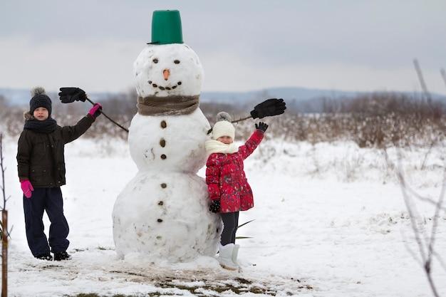 Twee schattige kinderen, jongen en meisje, staande voor lachende sneeuwpop in emmer hoed, sjaal en handschoenen op besneeuwde winterlandschap en blauwe hemel kopie ruimte achtergrond. vrolijk kerstfeest gelukkig nieuwjaar.