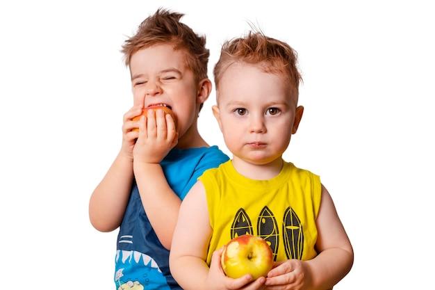 Twee schattige kinderen op de witte achtergrond, appels eten. geïsoleerd beeld.
